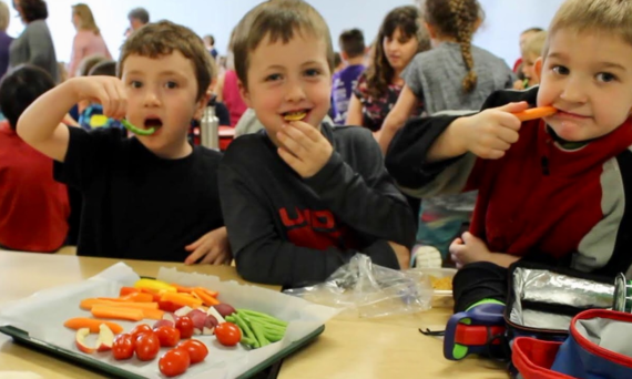 Three elementary students eating a healthy lunch